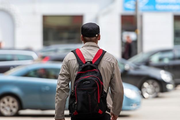 Widok z tyłu mężczyzny z plecakiem na nieostrym zbliżeniu tła ulicy