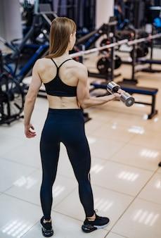 Widok z tyłu mięśni kulturysta w pełnym treningu wysokości z hantle w siłowni
