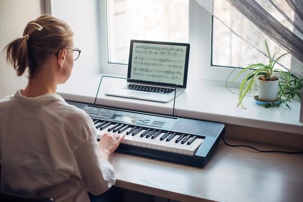 Widok z tyłu młoda kobieta gra na syntezatorze, czytając notatki na ekranie laptopa.