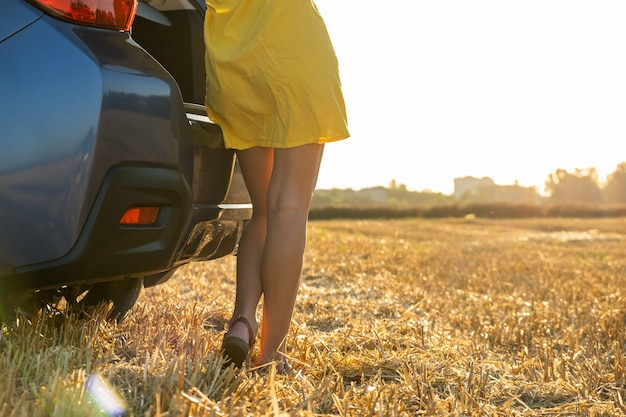Widok z tyłu młoda kobieta nogi kierowcy w żółtej letniej sukience stojącej w pobliżu jej samochodu.