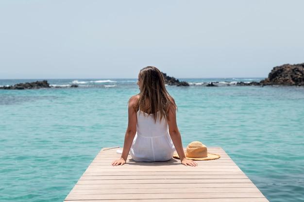 Widok z tyłu młoda kobieta patrząca na ocean