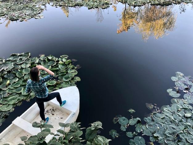 Widok z tyłu młoda kobieta ubrana w czarne spodnie i koszulę stojąc na głowie patrząc daleko na białej łodzi