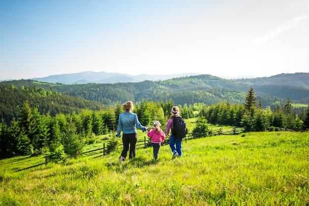 Widok z tyłu młoda matka i dwie córki schodzą w dół porośniętego zieloną trawą wzgórza