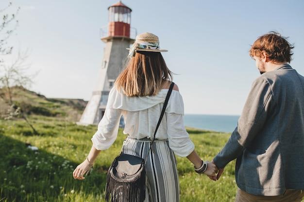Widok z tyłu młoda para hipster stylu indie zakochana chodzenie na wsi, trzymając się za ręce, latarnia morska na tle, ciepły letni dzień, słoneczny, czeski strój, kapelusz