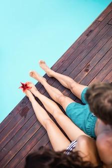 Widok z tyłu młoda para siedzi przy basenie w słoneczny dzień
