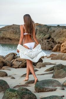 Widok z tyłu: młoda piękna kobieta ubrana w strój kąpielowy i białą koronkową pelerynę plażową zostaje w lecie w kurorcie