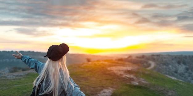 Widok z tyłu młoda szczęśliwa blondynka z czarną czapką, na szczycie wzgórz o zachodzie słońca. koncepcja podróży. zdjęcie panoramiczne z miejscem na kopię.