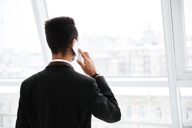 Widok z tyłu młodego afrykańskiego biznesmena w czarnym garniturze, rozmawiającego przez telefon i patrzącego na okno