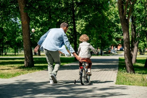 Widok z tyłu młodego aktywnego ojca pomagającego swojemu słodkiemu synkowi jeździć na rowerze, jednocześnie poruszając się drogą w publicznym parku między zielonymi trawnikami
