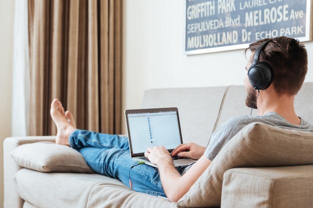 Widok z tyłu młodego człowieka w słuchawkach, leżącego na kanapie i słuchania muzyki z laptopa w domu