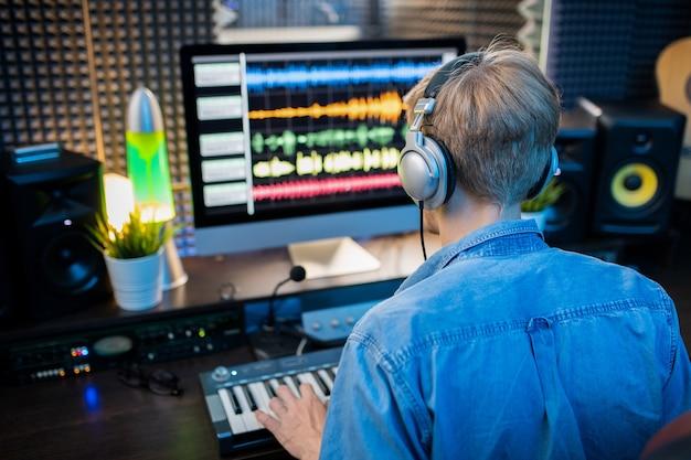 Widok z tyłu młodego człowieka w słuchawkach, patrząc na ekran komputera podczas tworzenia muzyki i nagrywania jej w nowoczesnym studio