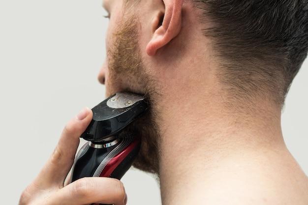 Widok z tyłu młodego hipster człowieka golenia brody imbir z golarką elektryczną. widok z tyłu
