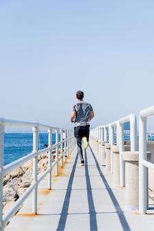 Widok z tyłu młodego mężczyzny biegnącego wzdłuż promenady w pobliżu morza?