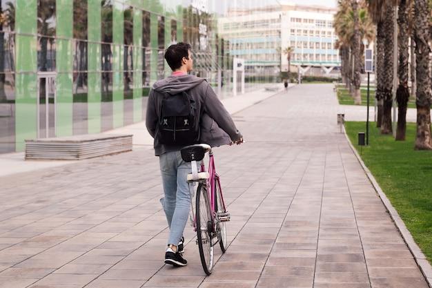 Widok z tyłu młodego mężczyzny idącego pchającego rower