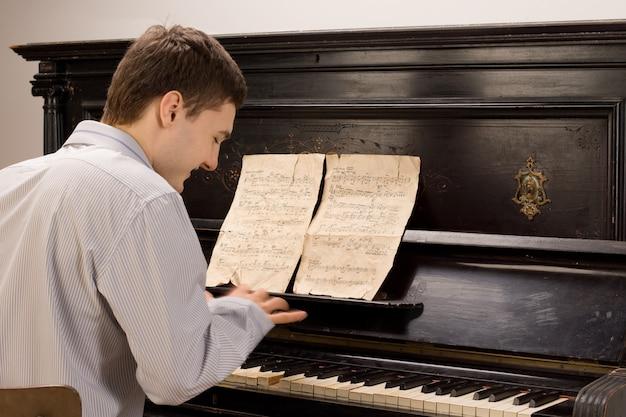 Widok z tyłu młodego mężczyzny uśmiechniętego podczas gry na pianinie