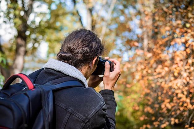 Widok z tyłu młodego mężczyzny z długimi włosami trzymającego aparat w dłoniach podczas robienia zdjęcia