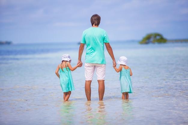 Widok z tyłu młodego ojca i jego dwóch uroczych córek na egzotyczne wakacje