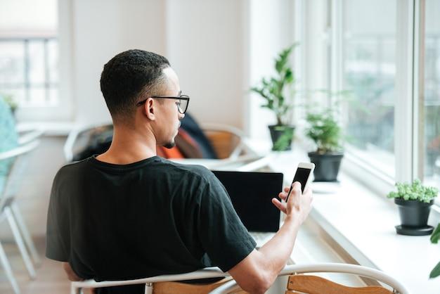 Widok z tyłu młodego studenta z telefonem komórkowym pracującym na laptopie podczas przerwy na kawę w kawiarni