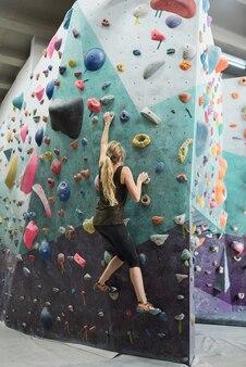 Widok z tyłu młodej aktywnej kobiety z długimi włosami, chwytającej sztuczne skały na ściance wspinaczkowej podczas poruszania się w górę