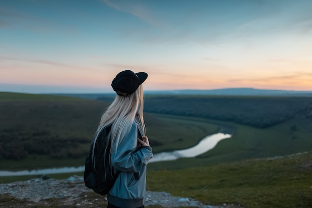Widok z tyłu młodej blondynki z plecakiem, podziwiając zachód słońca na szczycie wzgórz. koncepcja podróży.