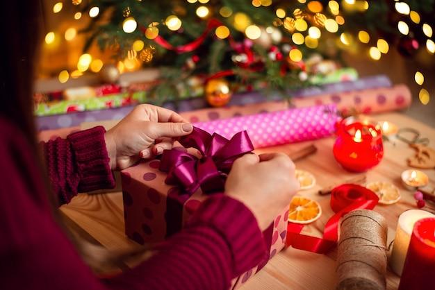 Widok z tyłu młodej dziewczyny przygotowującej prezenty dla bliskich osób