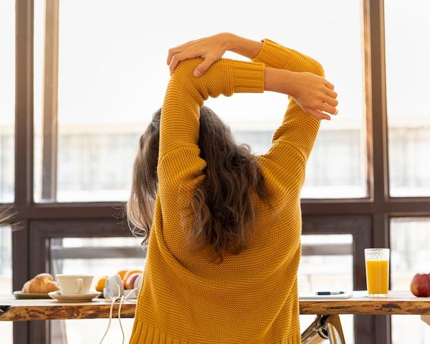 Widok z tyłu młodej kobiety bez twarzy ze sztywnymi mięśniami, napięciem i bólami stawów. rozciąganie kończyn, rozgrzewka, ćwiczenia w miejscu pracy, podciąganie