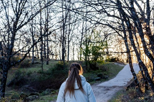 Widok z tyłu młodej kobiety blondynka z kucykiem trekking w naturalnym krajobrazie o zachodzie słońca.