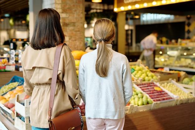 Widok z tyłu młodej kobiety i jej córki stojącej przed wyświetlaczem ze świeżymi owocami wewnątrz supermarketu