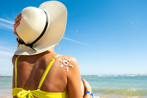 Widok z tyłu młodej kobiety opalanie się na plaży z kremem przeciwsłonecznym w kształcie słońca na jej ramieniu.