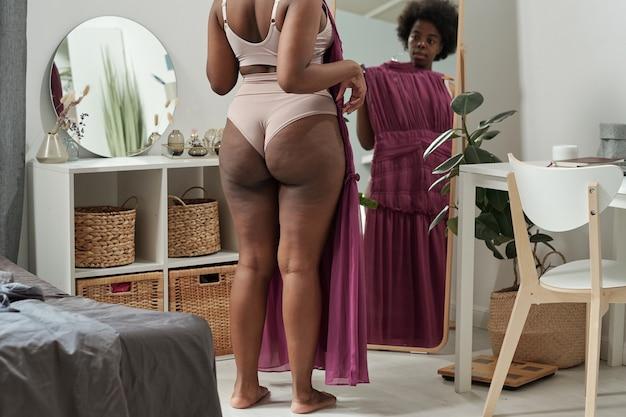 Widok z tyłu młodej kobiety plus size przymierza nową sukienkę