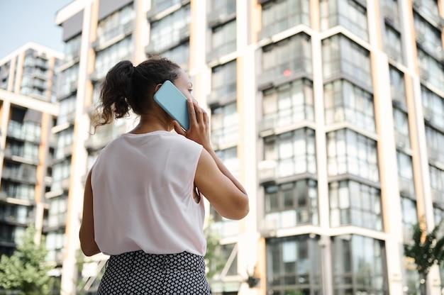 Widok z tyłu młodej kobiety rasy mieszanej african american rozmawia przez telefon komórkowy na tle miejskich wysokich budynków. koncepcje biznesowe i komunikacyjne