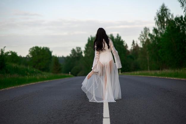 Widok z tyłu młodej kobiety w białej seksownej sukience stojącej na pustej linii asfaltowej wiejskiej drogi
