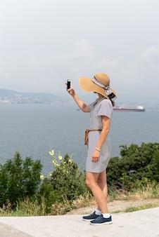 Widok z tyłu młodej kobiety w letniej sukience i kapeluszu robi zdjęcie panoramy miasta