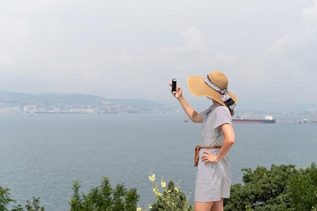 Widok z tyłu młodej kobiety w letniej sukience i kapeluszu robiącej zdjęcie panoramy miasta za pomocą telefonu komórkowego mobile