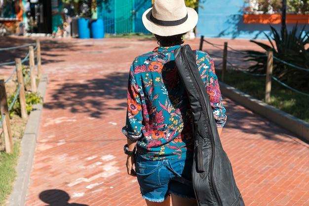 Widok z tyłu młodej kobiety z futerałem na gitarę, chodzącej po parku