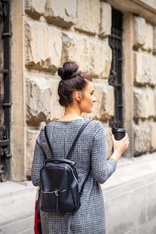 Widok z tyłu młodej kobiety z gorącym napojem i plecakiem spacery po europejskim mieście