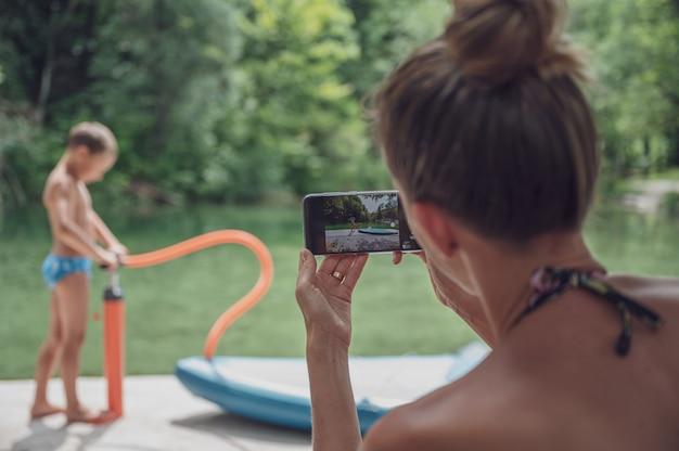 Widok z tyłu młodej matki robiącej zdjęcie z telefonem komórkowym synowi nad rzeką.