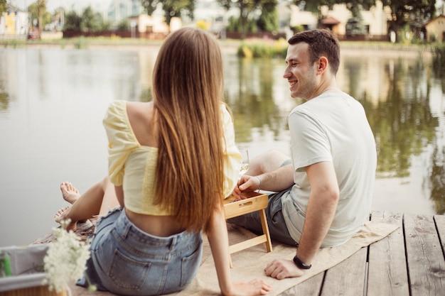 Widok z tyłu młodej pary na pikniku w pobliżu rzeki lub jeziora, kobieta i mężczyzna pijący razem wino na świeżym powietrzu, ludzie bawią się