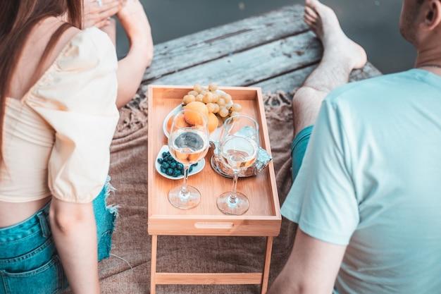 Widok z tyłu młodej pary na pikniku w pobliżu rzeki lub jeziora, kobieta i mężczyzna pijący wino na zewnątrz