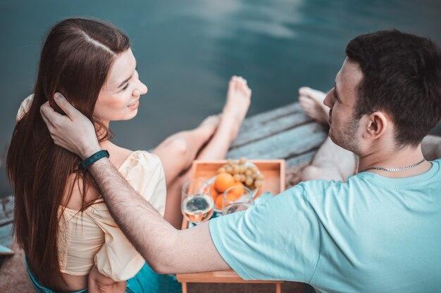 Widok z tyłu młodej pary na pikniku w pobliżu rzeki lub jeziora, kobieta i mężczyzna razem piją wino na zewnątrz, ludzie bawią się na letnie wakacje