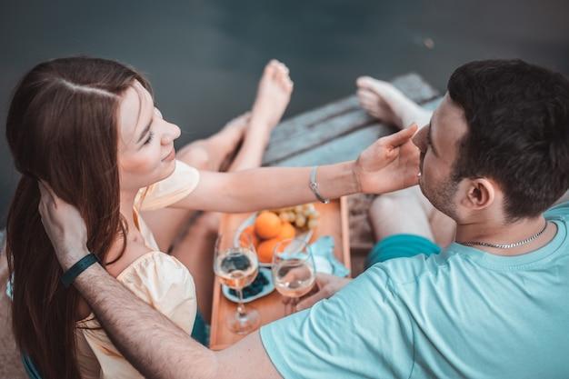 Widok z tyłu młodej pary na pikniku w pobliżu rzeki lub jeziora, kobieta i mężczyzna razem piją wino na zewnątrz, ludzie bawią się na wakacjach, miłosne emocje