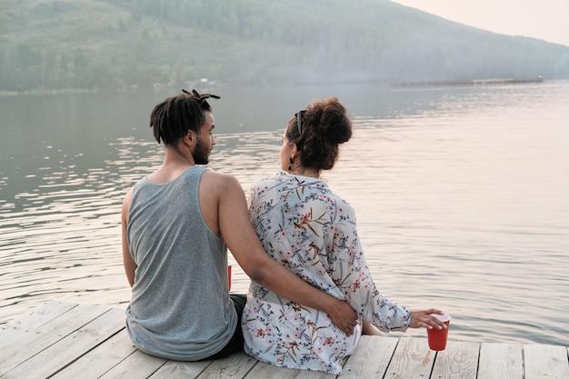 Widok z tyłu młodej pary obejmującej się i podziwiając piękny widok na jezioro, siedząc na molo
