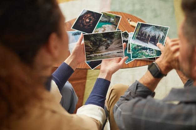Widok z tyłu młodej pary patrząc na swoje zdjęcia i wspominając szczęśliwe chwile