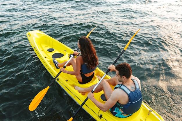 Widok z tyłu młodej pary, pływanie kajakiem po jeziorze