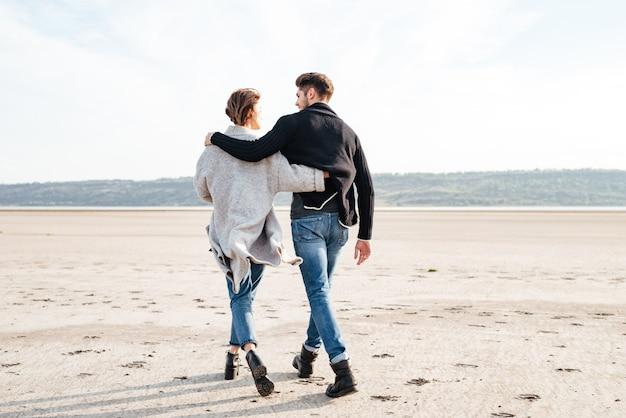 Widok z tyłu młodej pary przytulającej się i idącej wzdłuż plaży