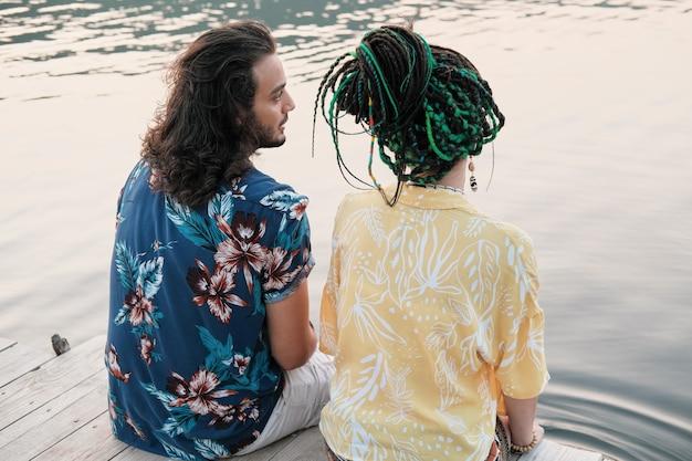 Widok z tyłu młodej pary rozmawiającej ze sobą siedząc na pomoście i mocząc stopy w wodzie