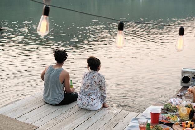 Widok z tyłu młodej pary siedzącej na molo i patrząc na widok na jezioro mają randkę na świeżym powietrzu
