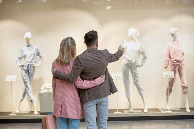 Widok z tyłu młodej pary stojącej przed witryną sklepu i omawiającej ubrania na manekinach razem w centrum handlowym