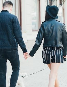 Widok z tyłu młodej pary w czarnych kurtkach trzymającej się za ręce z białym psem