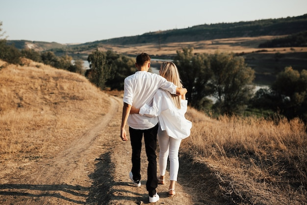 Widok z tyłu młodej pary zakochanych przytulanie podczas spaceru wzdłuż wiejskiej drogi z pięknym krajobrazem.